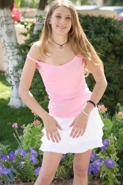 Smiling cutie Lisa Nubiles with sinistral top plus pushover white bird poses with the garden.