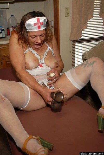 Granny nurse Ivee pulling white panties aside to toy mature pussy
