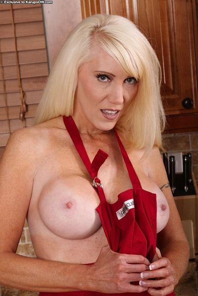 Older blond lady Krystal Day revealing big round tits and pink cunt in kitchen