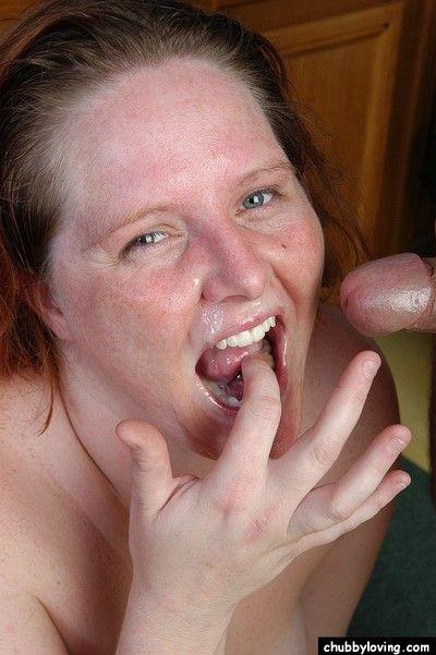Older redheaded fatty Adrienne taking blast of jism on pierced tongue