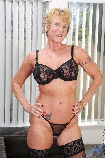 Stocking and lingerie clad gran Honey Ray baring big tits and masturbating