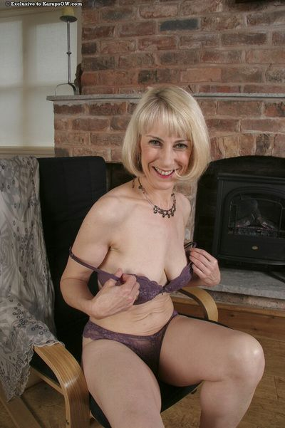 Sexy bodied mature blonde Hazel May eagerly exposes her bush after striptease