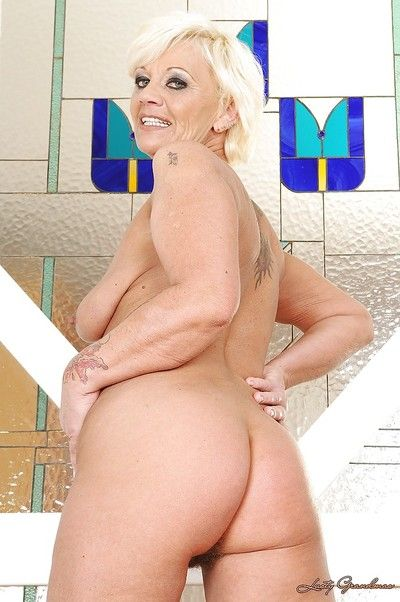 Horny granny stripping off her lingerie and toying her shaggy cunt