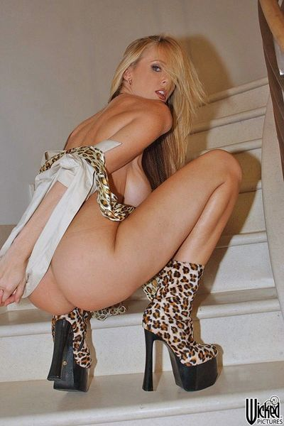 Busty blonde Julia Ann is wearing nothing but leopard high heeled boots as posing on the stairs