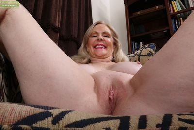 Older blonde female Judy Belkins removing black hose to bare shaved twat