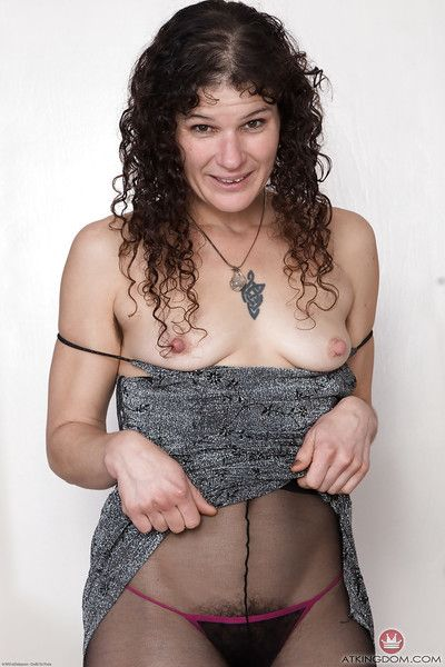 Hirsute model Sunshine freeing hairy mature cunt from black pantyhose