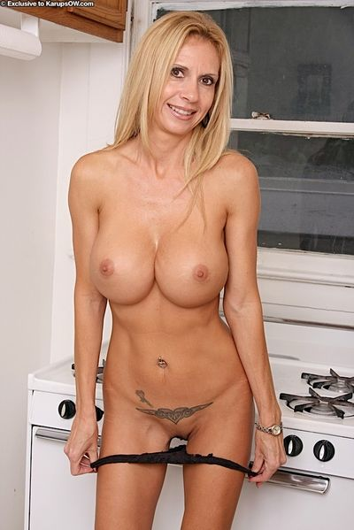 Mature woman Brooke Tyler unveiling massive fake boobs in kitchen