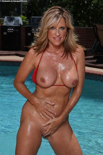 Older blonde woman Jodi West releasing big natural boobs from bikini in pool