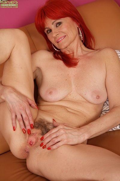 Older redhead Amanda Rose freeing beaver from panties before masturbating