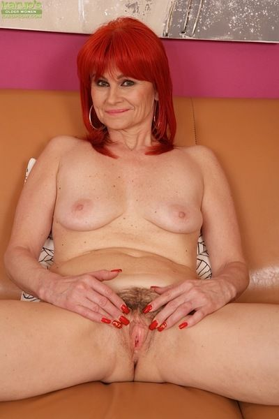 Older redhead Amanda Rose freeing beaver from panties before masturbating