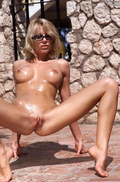 Seducing blonde milf Holly Sampson is on the golden sand masturbating pussy until pee