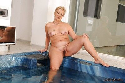 Short haired fatty granny stripping off her lingerie and posing in the pool