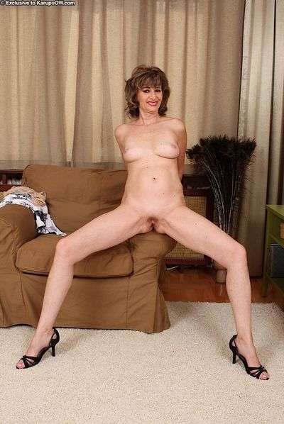 Leggy older lady Judy stretching labia lips wide open after undressing