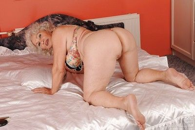 Big busted granny stripping off her lingerie and posing naked
