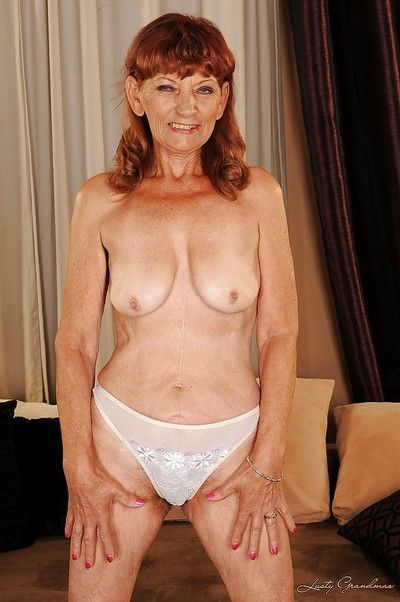 Redhead granny on high heels stripping and exposing her bushy cunt