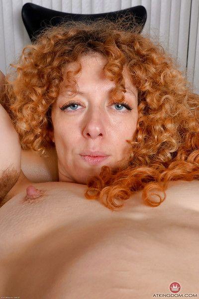 Leggy experienced redhead Leona spreading hairy pink pussy