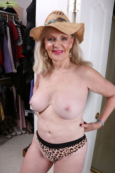 Chubby aged blonde Judy Belkins unveiling big mature tits in straw hat