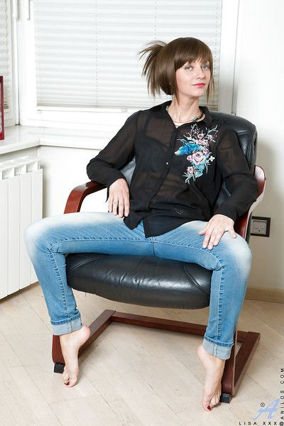 Barefoot mature brunette in jeans baring small tits while undressing