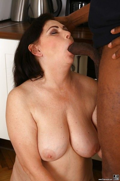 Busty granny Tilda giving black cock oral sex before interracial fucking