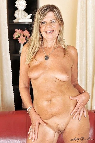 Filthy granny taking off her clothes and posing naked on the sofa