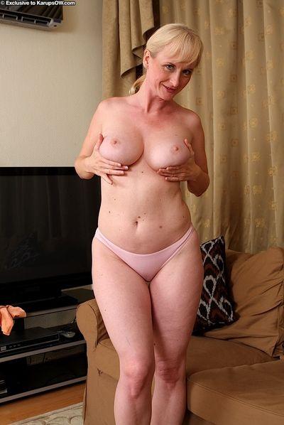Big boobed older blonde Monik displaying pink cunt after undressing