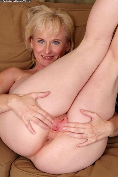 Big boobed older blonde Monik displaying pink cunt after undressing