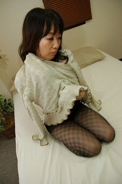 Asian lady in pantyhose Yukiko Moritani undressing and posing on the couch