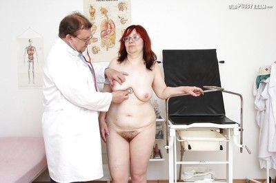 Redhead granny in glasses gets her twat examed by naughty gyno