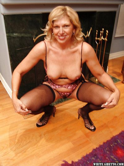 Lustful granny in stockings gets rid of her formal suit and reveals her tits