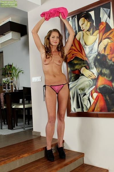 Mature broad Michelle Gaia spreads shaved cunt after stripping naked