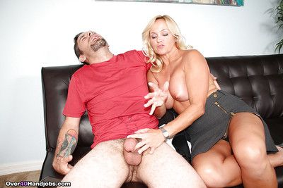 Blonde cougar goes topless while coaxing cum from fat cock via handjob