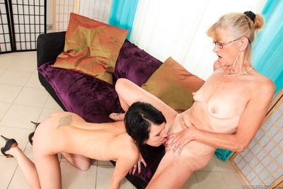 Naughty granny in glasses seducing young brunette for lesbian sex