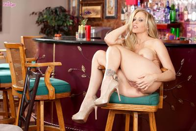 Curvy blonde milf Julia Ann with massive tits and smooth snatch strips naked at the bar