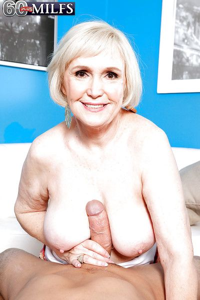 Blond oldie Lola Lee squeezing a stiff cock between her massive hooters