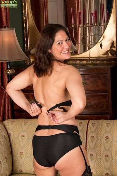 Experienced lady in stockings and garters frees big boobs from lingerie
