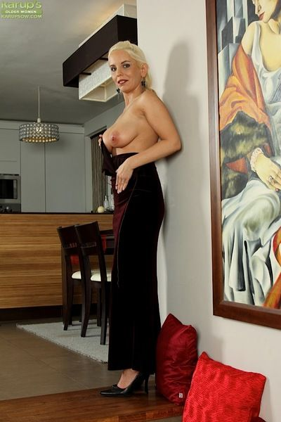 Clothed mature blonde Sandy Figgs posing nude in high heels after stripping