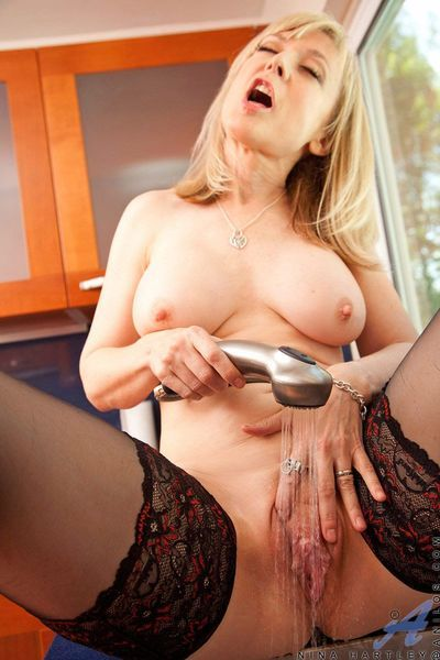 Busty milf in stockings Nina Hartley stimulates the clit with the help of water streams