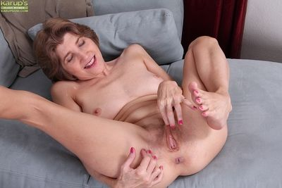Older babe Bossy Ryder strips naked and spreads hairy granny cunt
