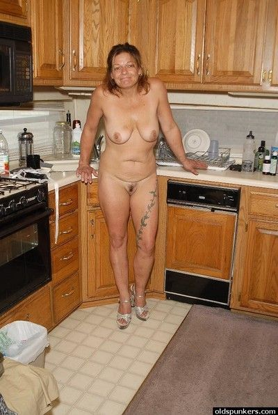 Granny Ivee showing off tattoos and shaved mature vagina in kitchen