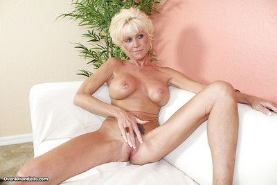Lustful mature blonde gives some handjob pleasure to a little man