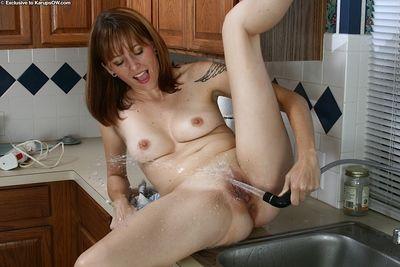Older lady Pandora wetting shaved vagina under the kitchen tap