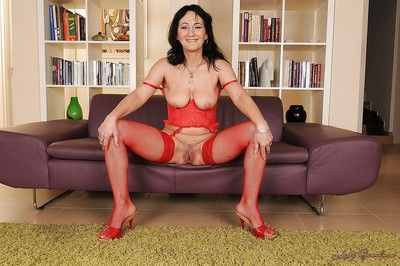 Lusty granny in lingerie and stockings uncovering her tits and twat