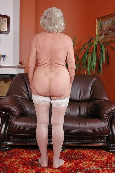 Lustful granny in white stockings masturbating her twat with a big dildo