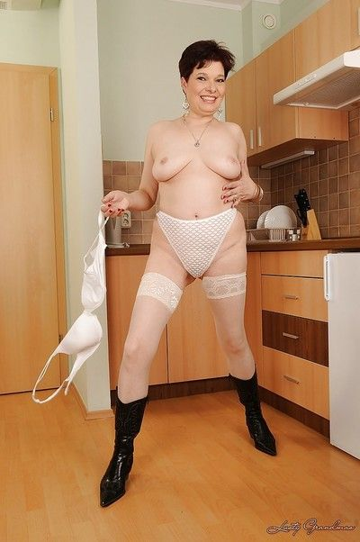 Naughty brunette granny with flabby boobs stripping in the kitchen
