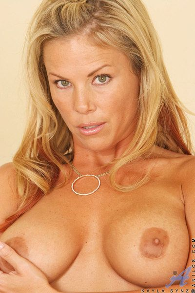 The horny blonde milf Kayla Synz playing around naked in her own bedroom