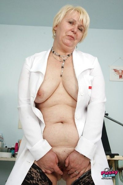 Naughty granny in nurse uniform stretching her twat by her fingers