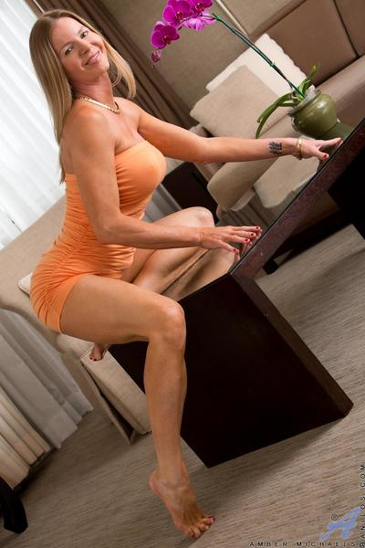 Charming busty milf Amber Michaels gets rid of her panties and shows it all in the living room