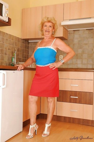 Lecherous blonde granny with round jugs stripping in the kitchen