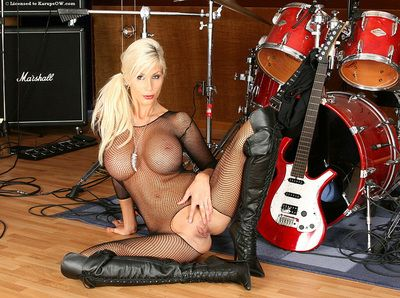 Busty blonde porn star Puma Swede in mesh body stocking and leather boots plays the guitar