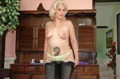 Granny with big tits takes off jeans to show her tattoo and her cunt